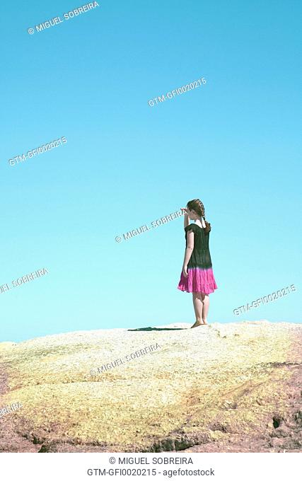 Girl Standing on Rock Looking Out