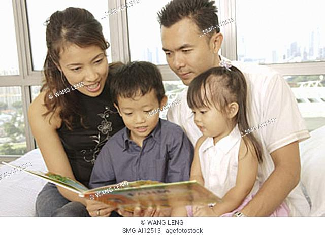Family with two children sitting together, looking at book