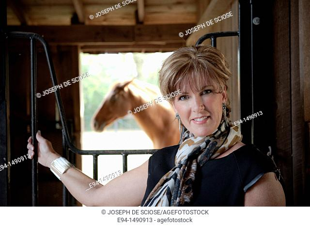 Portrait of a 52 year old blonde woman in casual black dress in a horse barn setting looking at the camera with a horse in the background