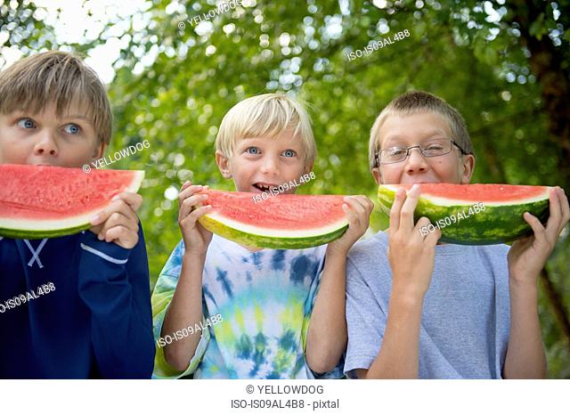 Friends eating watermelon in garden