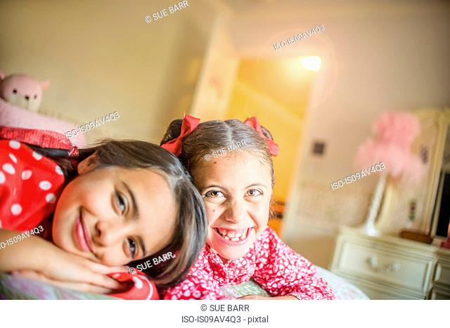 Portrait of two happy sisters lying on bed