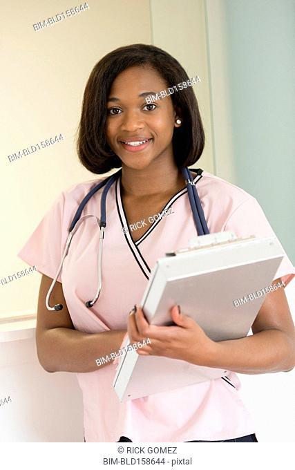 Mixed race nurse holding medical chart