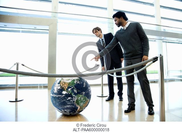 Businessmen looking at ball in lobby