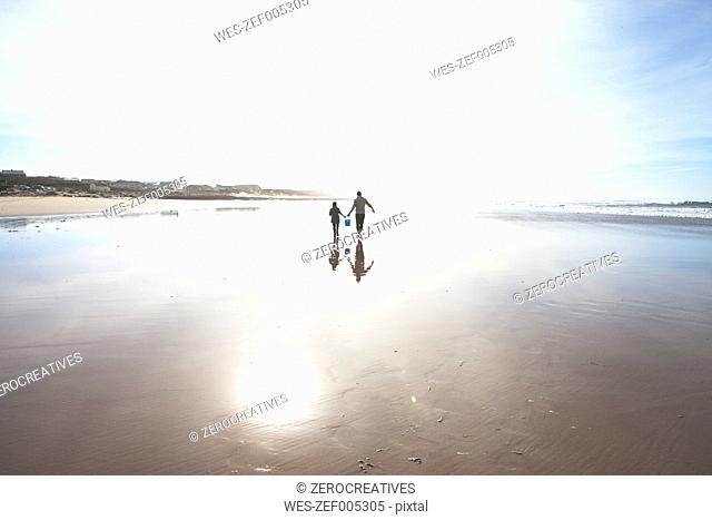 South Africa, Witsand, father and son walking on the beach at backlight