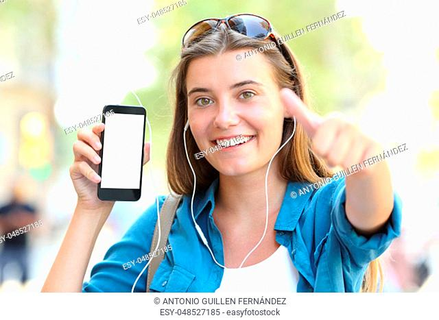 Happy girl listening to music showing blank smart phone screen gesturing thumbs up in the street
