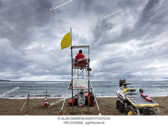 Las Canteras beach, Las Palmas, Gran Canaria, Canary Islands, Spain. A lifeguard under a stormy sky looks out over an empty city beach as heavy rain passes over...