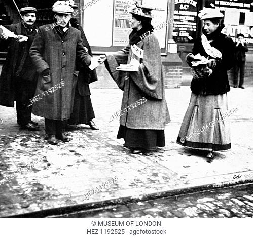 Suffragettes handing out leaflets, London, October 1907. Wearing 'Votes for Women' sashes, the suffragettes hand campaign materials to men in flat caps