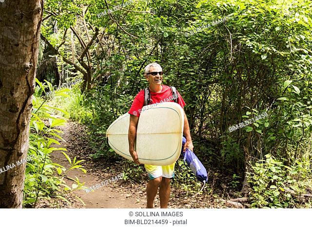 Caucasian man carrying surfboard in jungle
