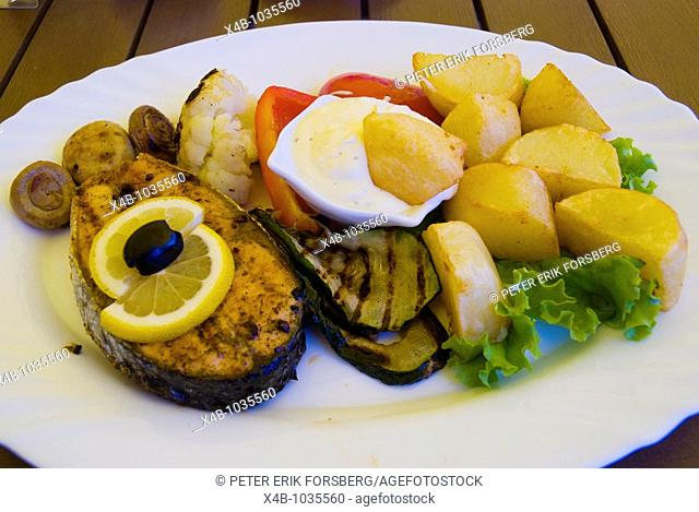 Grilled salmon steak and oven potatoes in a restaurant in Klaipeda Lithuania Europe