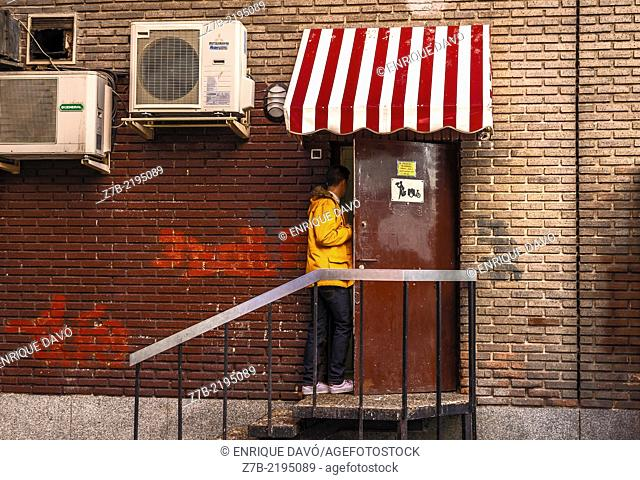 View of a yellow jacket of a man in the back gate of a bar, Madrid city, Spain