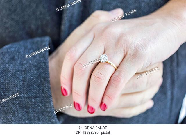 Diamond engagement ring with couple's hands clasped; Surrey, British Columbia, Canada