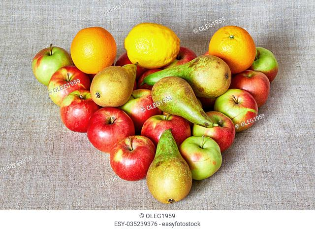 Apples, pear, orange and lemon lies on a gray canvas