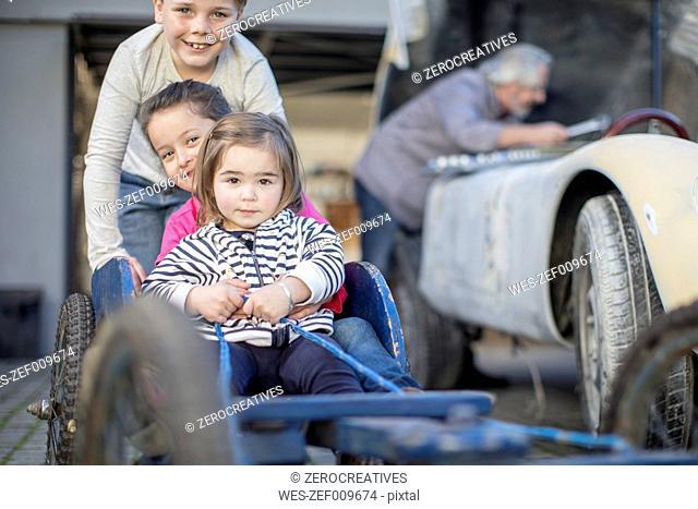 Boy pushing two little girls in go-kart