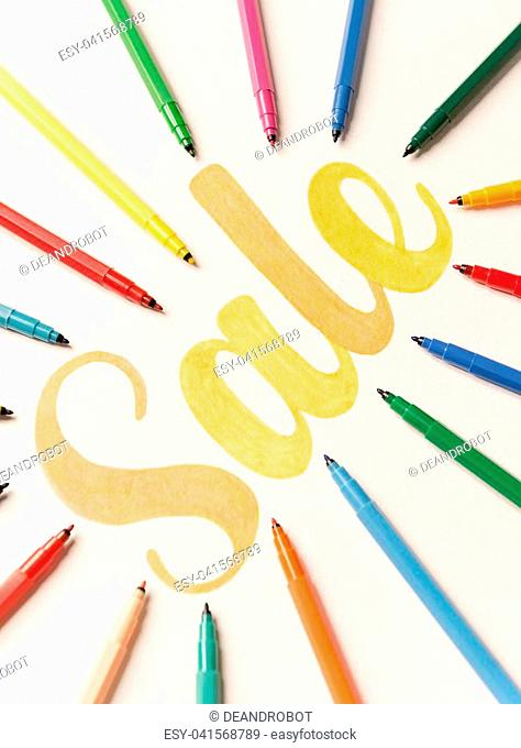 Picture of hand written calligraphy lettering 'Sale' with orange markers on white paper