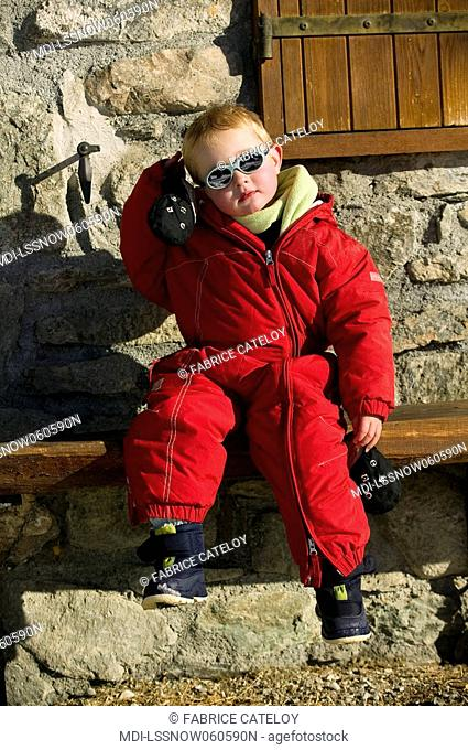 Young boy in ski clothes and with sun glasses sitting in the sun