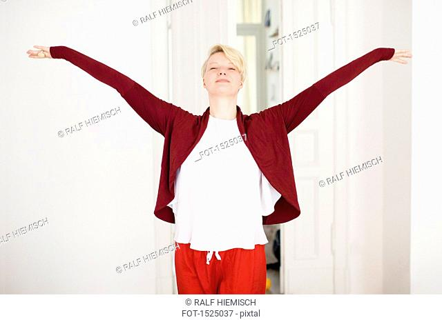 Relaxed mid adult woman with arms outstretched at home