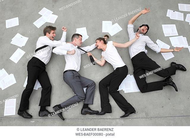 Three business people in a quarrel, woman pulling man's ties, elevated view