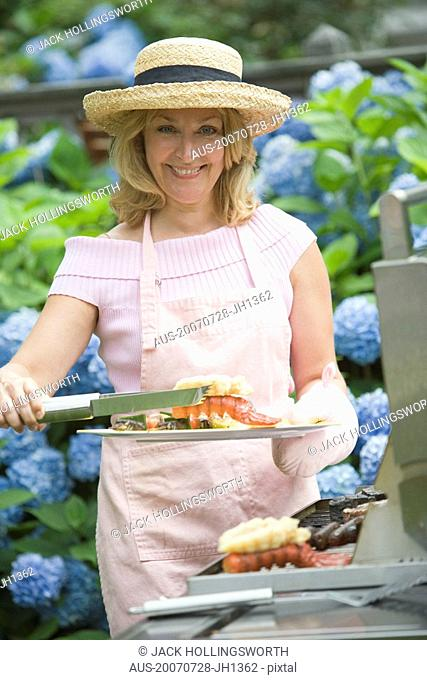 Mature woman preparing food on a barbecue grill and smiling