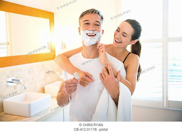 Playful wife wiping shaving cream on husband's face in bathroom