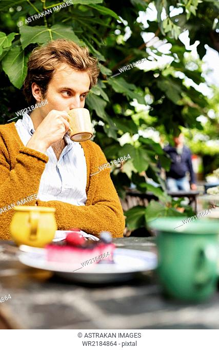 Man drinking coffee with cake served on table at greenhouse
