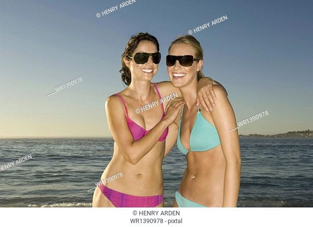 Two young women on the beach in Cape Town, wearing bikinis and sunglasses