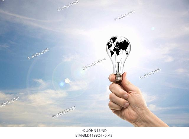 Caucasian man holding globe light bulb