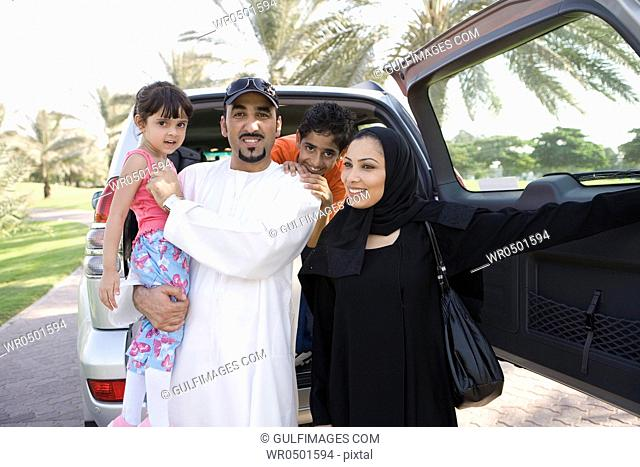 Father and mother with children standing in front of car, smiling
