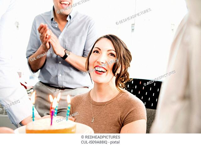 Female office worker receiving birthday cake
