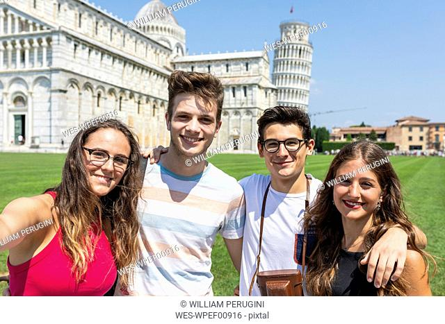 Italy, Pisa, portrait of friends with the Leaning Tower in background