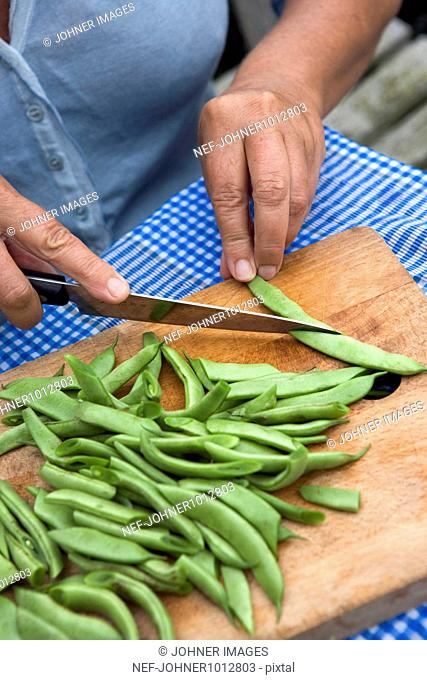 Woman cutting beans on chopping board