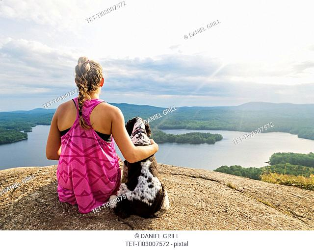 Young woman sitting with dog on cliff looking at lake view