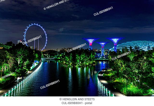 Blue ferris wheel and Supertree Grove on Marina Bay waterfront at night, Singapore, South East Asia