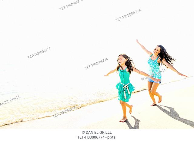 View of girl (6-7) and her mom running on beach