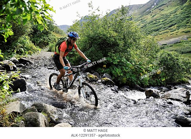 Woman rides a full suspension mountain bike across a stream on the Devil's Pass Trail in the Chugach National Forest, Kenai Peninsula, South-central Alaska