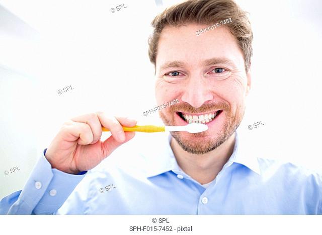 MODEL RELEASED. Man brushing teeth, portrait, close-up