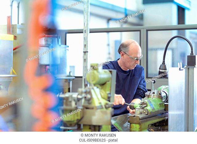 Senior engineer making precision parts at traditional lathe in engineering factory