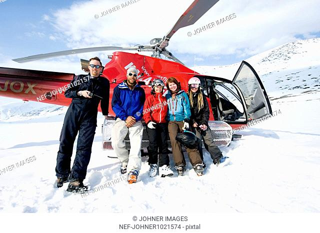 Group of people posing while leaning on helicopter