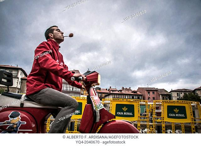 A man, carries an egg with a spoon in his mouth, while driving a scooter, in a contest of skill during Llanes scooters concentration. Asturias, Spain