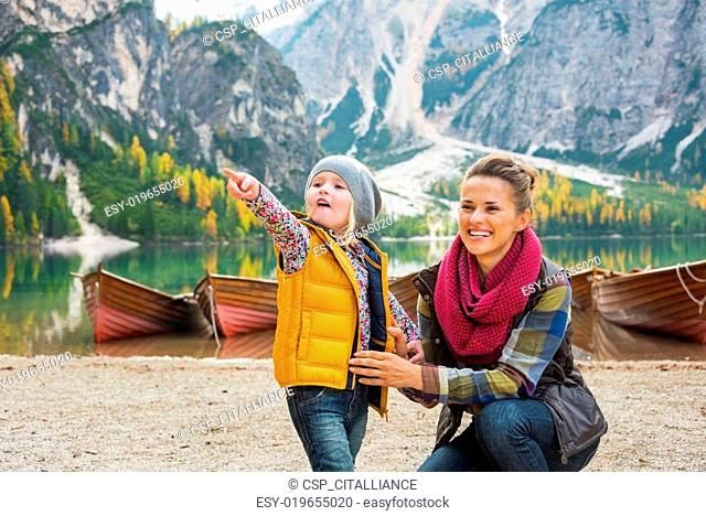 Mother and baby pointing while on lake braies in south tyrol, it