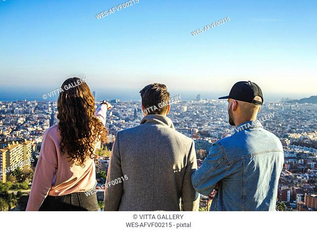 Spain, Barcelona, three friends on a hill overlooking the city