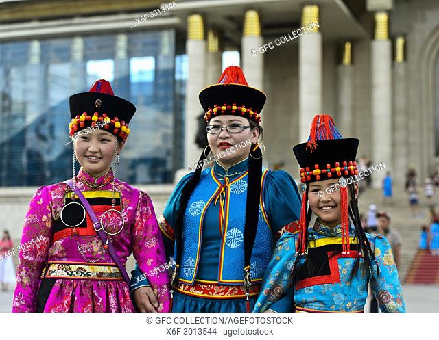 Three young women pose in traditional deel costume and the typical hat with the cone shaped top, Mongolian National Costume Festival, Ulaanbaatar, Mongolia