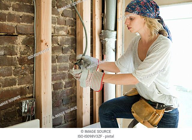 Woman wearing protective gloves working with wiring