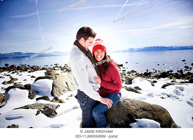 Couple sitting by snowy lake laughing