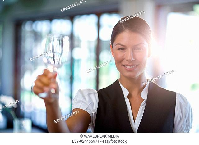 Waitress holding up a empty wine glass