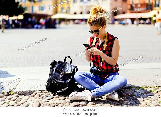 Italy, Verona, woman on town square looking at cell phone