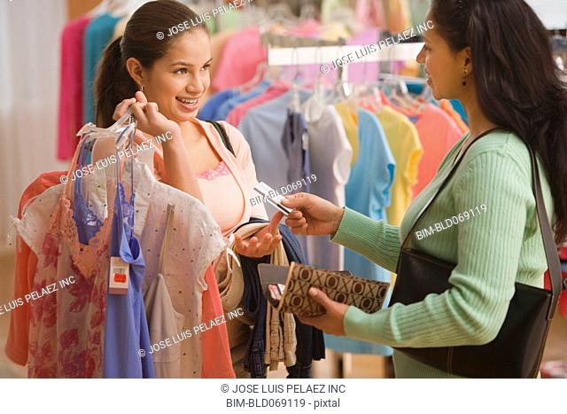 Hispanic mother giving daughter credit card to buy clothing