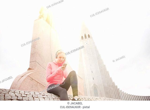 Low angle view of teenage girl wearing headphones sitting by Hallgrímskirkja, Reykjavik, Iceland