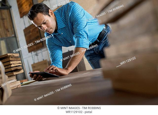 A young man in a workshop which uses recycled and reclaimed lumber to create furniture and objects. Using a digital tablet in his work