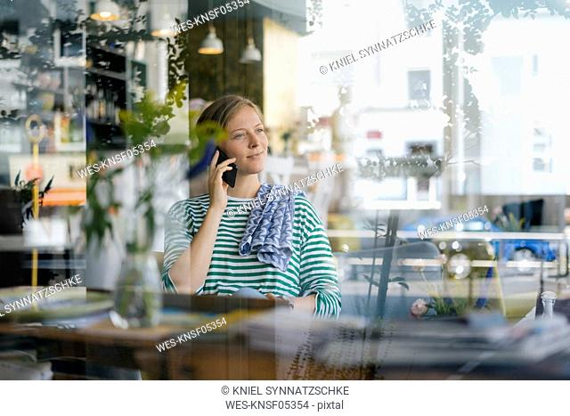 Smiling young woman on cell phone in a cafe