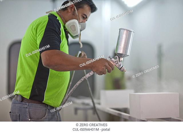 Man spraying wooden products in carpenters workshop
